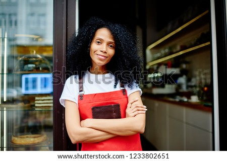 Half length portrait of cheerful african american professional barista in red apron smiling at camera.Positive dark skinned female waitress with crossed hands standing at entrance to own coffee shop Foto d'archivio ©