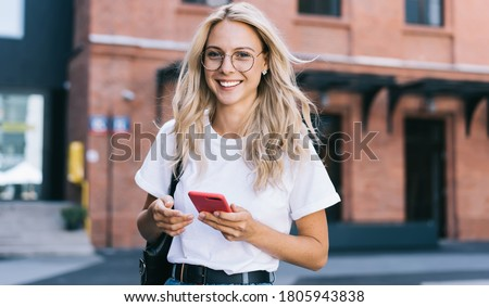 Half length portrait of cheerful caucasian female in trendy wear spending time on street using smartphone, beautiful millennial hipster girl blogger looking at camera in town holding mobile phone Foto stock ©