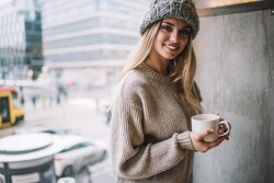 Half length portrait of cheerful female customer with coffee cup enjoying recereation time and warming beverage, happy Caucasian girl in knitted hat holding hot tea and smiling near cafeteria window