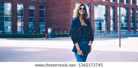 Half length portrait of cheerful female student walking around university campus with folder in hand, happy smiling hipster girl in trendy jeans posing and looking at camera on publicity area