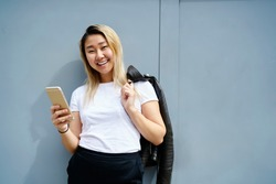 Half length portrait of cheerful female using mobile phone outdoors looking at camera and smiling, happy Japanese hipster girl in white t-shirt with copy space for brandname holding cellular