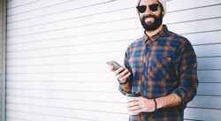 Half length portrait of cheerful hipster guy holding mobile technology and takeaway caffeine beverage and smiling at camera during vacations trip, happy Middle Eastern male blogger with cellular
