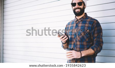 Half length portrait of cheerful hipster guy holding mobile technology and takeaway caffeine beverage and smiling at camera during vacations trip, happy Middle Eastern male blogger with cellular Stock photo ©