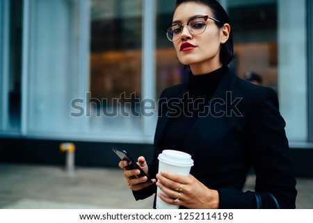 Half length portrait of confident financial economist in optical eyewear waiting for call from business partner while standing on urban setting with coffee to go in hand, concept of entrepreneurship #1252114198