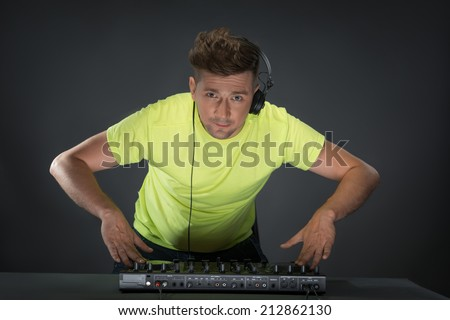 Half-length portrait of confident young DJ with stylish haircut and headphones on head spinning and mixing music on mixer while standing isolated on dark background