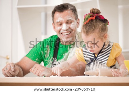 Half-length portrait of cute little daughter with handsome father cooking pastry, working with rolling pin. Dirty aprons