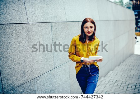 half length portrait of cute positive hipster girl looking at camera while standing next to wall with copy space for your advertising message and sending messages to friends via digital tablet #744427342