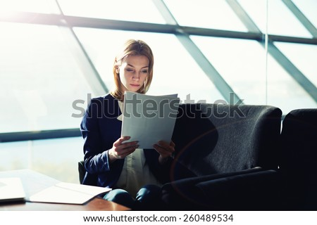 Half length portrait of female managing director examining paperwork in bight light office interior, attractive business woman read some documents before meeting, soft focus, filtered image