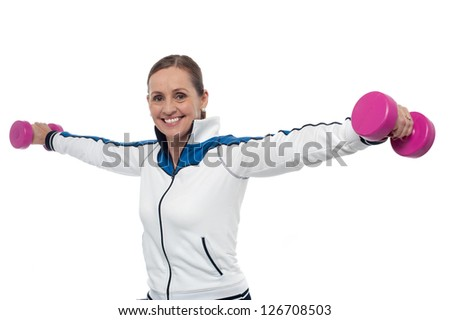 Half length portrait of fit middle aged woman holding dumbbells in her outstretched arms.