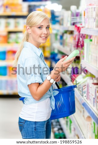 Half length portrait of girl at the market choosing cosmetics among the great variety of products. Concept of consumerism, retail and purchase
