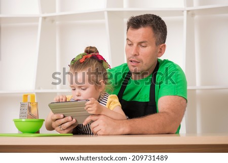 Half length portrait of handsome father and cute little daughter wearing aprons, cooking with tablet, grater and kitchen cutting board. Cooking or technology and food concept