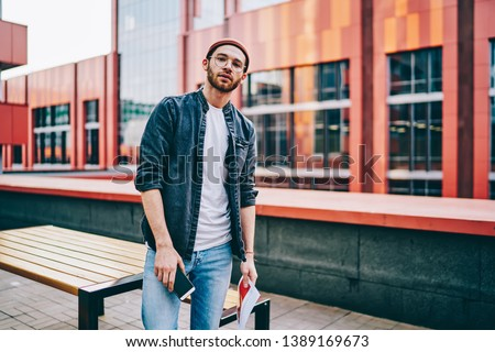 Half length portrait of handsome man in jeans apparel standing on urban setting background, serious  caucasian hipster guy looking at camera dressed n trendy casual street style wear and spectacles Foto stock ©