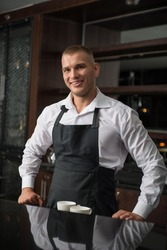 Half-length portrait of handsome young smiling barista wearing white shirt and black apron leaning on the bar counter and looking at us