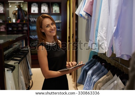 Half length portrait of happy female entrepreneur using digital tablet for job in her modern store with men\'s clothes, smiling woman owner or consultant holding touch pad while standing in brandy shop