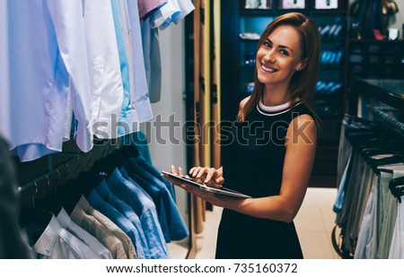 Half length portrait of happy female entrepreneur using digital tablet for job in her modern store with men's clothes, smiling woman owner or consultant holding touch pad while standing in brandy shop