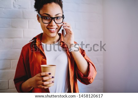 Half length portrait of prosperous hipster girl in optical spectacles for provide eyes protection making positive smartphone conversation with best friend during break for enjoying caffeine beverage