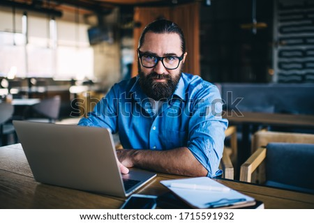 Half length portrait of serious bearded male in eyewear concentrated on remote job looking at camera, concentrated mature man 20s freelancer using laptop computer for online research in cafe