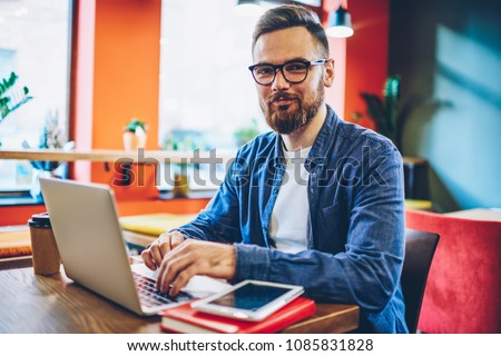 Half length portrait of successful bearded designer smiling at camera while working on freelance at netbook.Happy businessman keyboarding on laptop computer checking database via wireless internet #1085831828