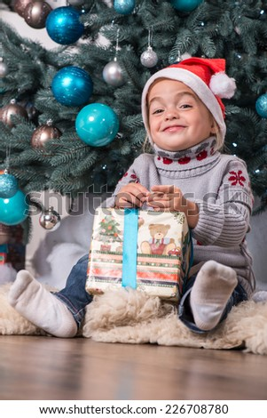 Half-length portrait of the little cute fair-haired smiling girl sitting on the floor near Christmas presents wearing warm sweater and red cap of Santa Claus unpacking her nice present