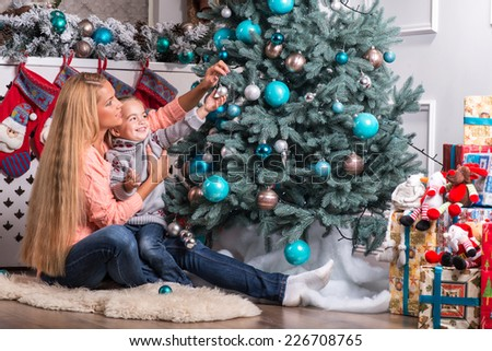 Half-length portrait of the little cute fair-haired smiling girl with her lovely mom wearing warm sweaters and jeans sitting aside near the Christmas tree decorating it
