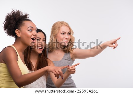 Half-length portrait of three young lovely girls wearing colorful T-shirt looking and pointing at someone with surprise. Isolated on white background