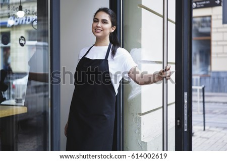 Half length portrait of waitress dressed in black apron with copy space for brand name open store starting work ready to serve visitors, woman entrepreneur barista standing at restaurant entrance