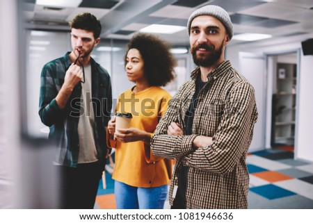 Half length portrait of young bearded positive professional IT developer standing near to colleagues at daily meeting.Smiling male person looking at camera while partners communicating about project