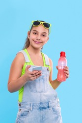 Half length portrait  of young brunette smiling girl wearing  denim overalls shorts and green sunglasses standing with a phone and with a bottle of water.  Vacation and reacriation concept
