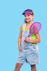 Half length portrait  of young brunette smiling girl wearing  denim overalls shorts and sun shade standing with a tennis racket in his hands. Vacation and reacriation concept