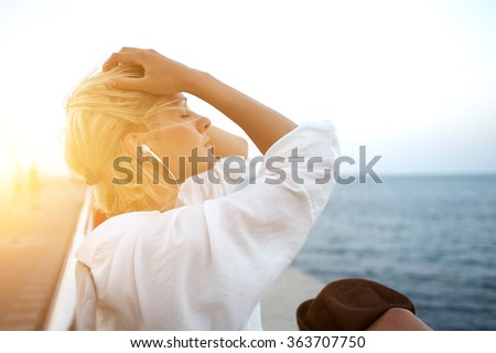 Half length portrait of young charming woman in headphones relaxing while sitting near ocean in summer evening, attractive carefree female listening favorite music during recreation time in weekend