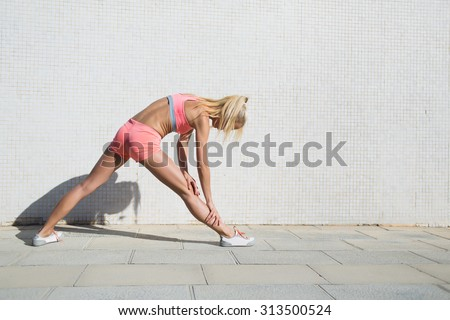 Half length portrait of young female runner stretching her muscles before begin training session in the fresh air, fit woman in sportswear stretching legs against street wall with copy space for text