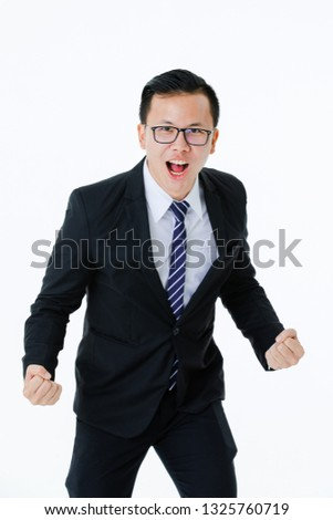 Half-length portrait of young handsome Asian man wearing eyeglasses in business suit posing triumphant with clenched fists and broad smile looking at camera, on isolated white background