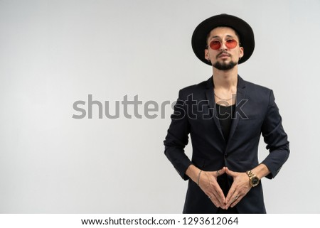 7bf75d7fbec Half length portrait of young handsome serious modern male wearing black  suit and hat in round