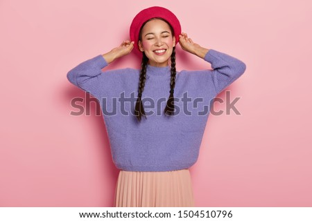 Half length shot of happy Asian woman touches beret, smiles pleasantly, shows white teeth, has two pigtails, wears purple jumper and skirt, expresses pleasant feelings, isolated over pink background