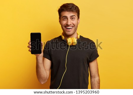 Half length shot of optimistic man holds smartphone with mock up screen, listens favourite soundtrack in headphones, wears casual black t shirt, stands indoor. People and technology concept.