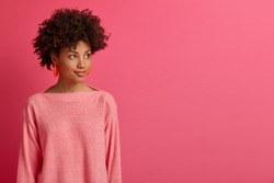 Half length shot of pensive dark skinned African American woman turns away, focused somewhere, considers better ways, has something on mind, wears long sleeved jumper, isolated on pink backgroud