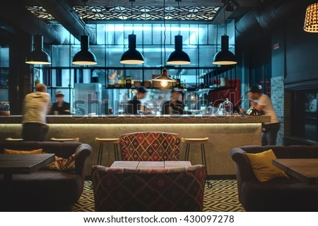Half-lighted hall in a loft style in a mexican restaurant with open kitchen on the background. In front of the kitchen there are wooden tables with multi-colored chairs and sofas. On the sofas there