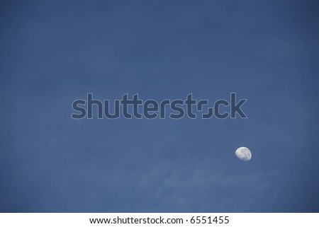 Half moon against a blue sky.