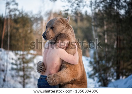 Half-naked man hugs a brown bear in a winter forest. Bear hugs man in response. The theme of the friendship of man and animal.