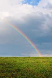 Half of a bright rainbow shines over a grassy field with blue sky and puffy clouds