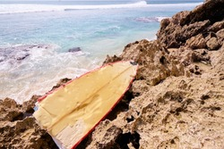 Half of a broken vanilla-red surfboard left behind on a dead rift remains on the beach.