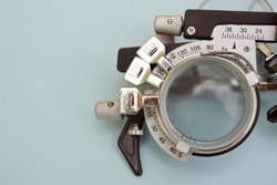 Half of a test glasses for high myopia. This optician instrument contains three lens on. Vision care background.
