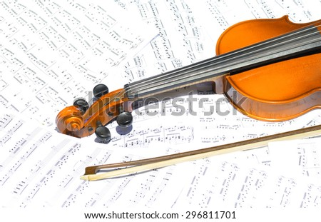 Half of an old violin with its bow lying on a pile of white sheet music