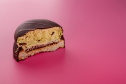 Half of biscuit cookie in chocolate glaze or frosting with jam inside on pink background. Sweet tasty unhealthy snack. Copy space.