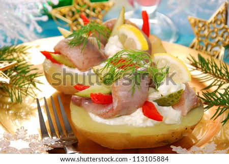 half of boiled potato with herring fillet,sour cream and cheese as appetizer for christmas