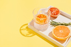 Half of grapefruit and bloody orange, rosemary on a white wooden tray and glass with water on bright yellow background. Summer refreshment concept. Sunlit flat lay. Minimal style. Top view.