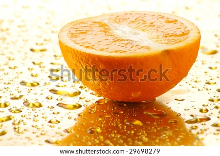 Half of juicy orange is on a surface. It is a lot of water