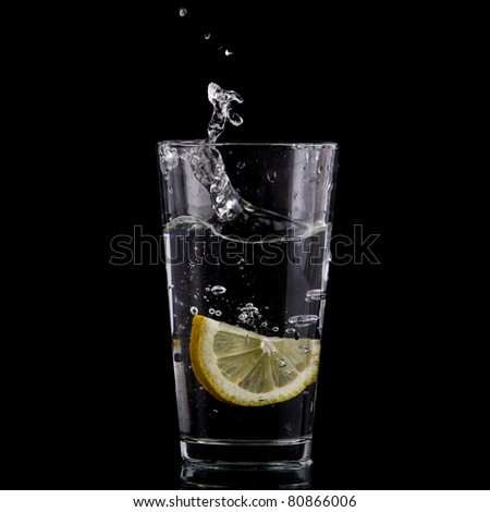 Half of lemon falling down in glass with water on deep black.  Beautiful glass with sparkling water or other transparent drink and a slice of lemon on black background