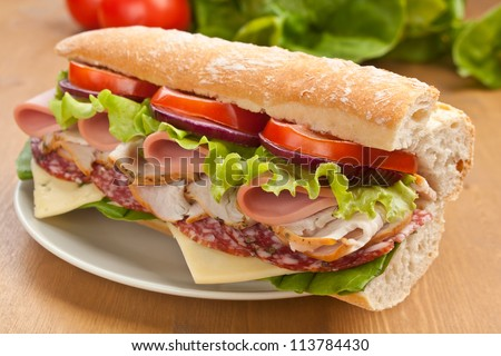 Half of long tasty subway baguette sandwich with lettuce, tomatoes, ham, turkey breast, salami and cheese