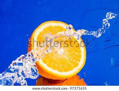 Half of orange in water splash - stock photo
